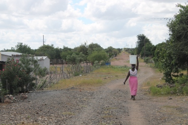 Young woman collecting water from communal standpipe (photo: Sally Rangecroft)